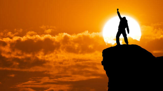 person standing on high rock with arm raised at sunset