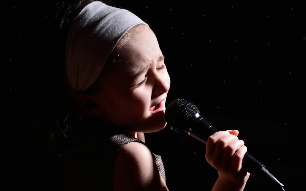 young girl singing into mic