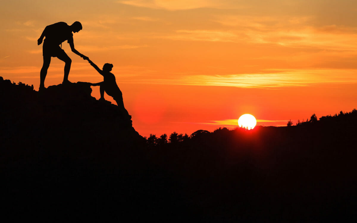 people climbing at sunset