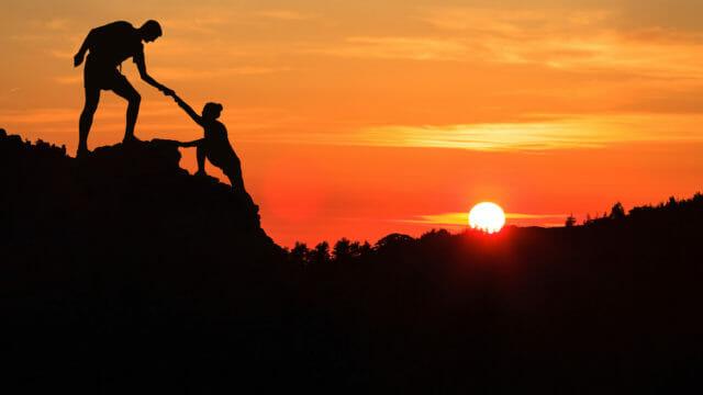 people climbing at sunset